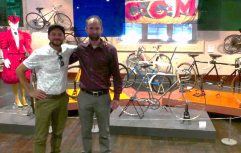 Friends standing proudly in front of bicycle display.